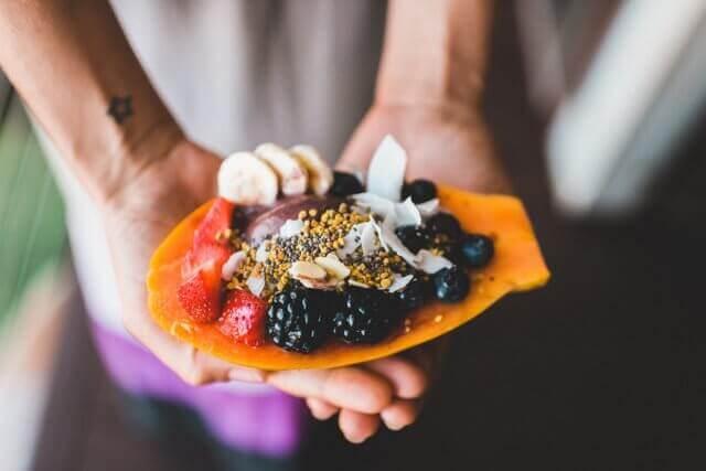 Salade de fruits: graines, mures, fraises, bananes, noix de coco dans une mangue