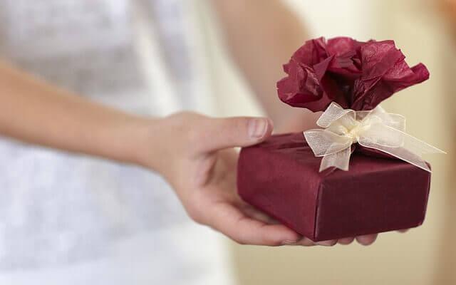 Cadeau avec ruban doré et papier bordeau tenu à la main