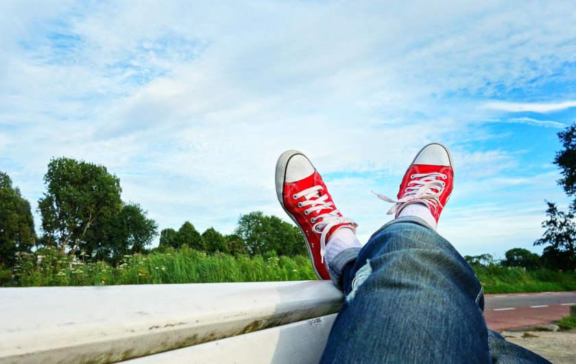 Jambes croiées avec tennis rouge sur fond de ciel bleu. Décontracté.
