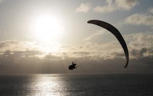 Parapente sur fond de mer et soleil couchant.
