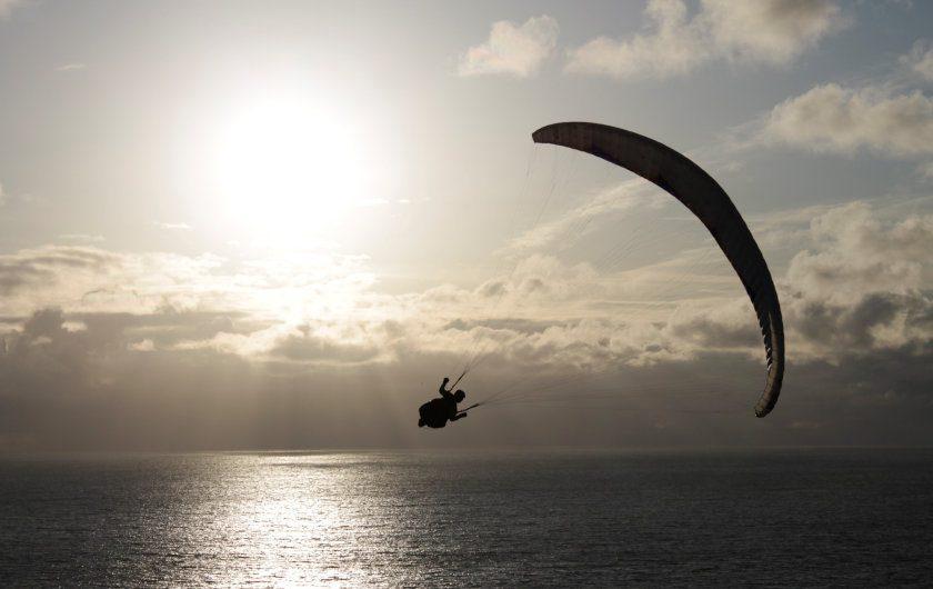Parapente sur fond de mer et soleil couchant