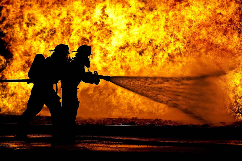 Silhouette de deux pompiers devant un mur de feu arrosant les flammes.