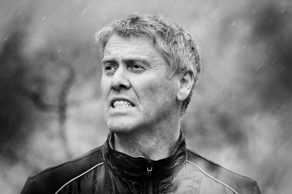 Homme d'âge moyen l'air tendu sous la pluie. Photo noir et blanc avec un arrière-plan flou.